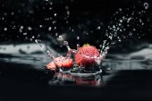 reife Erdbeeren, die ins Wasser fallen