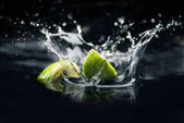 Fotografie slices of lime falling in water