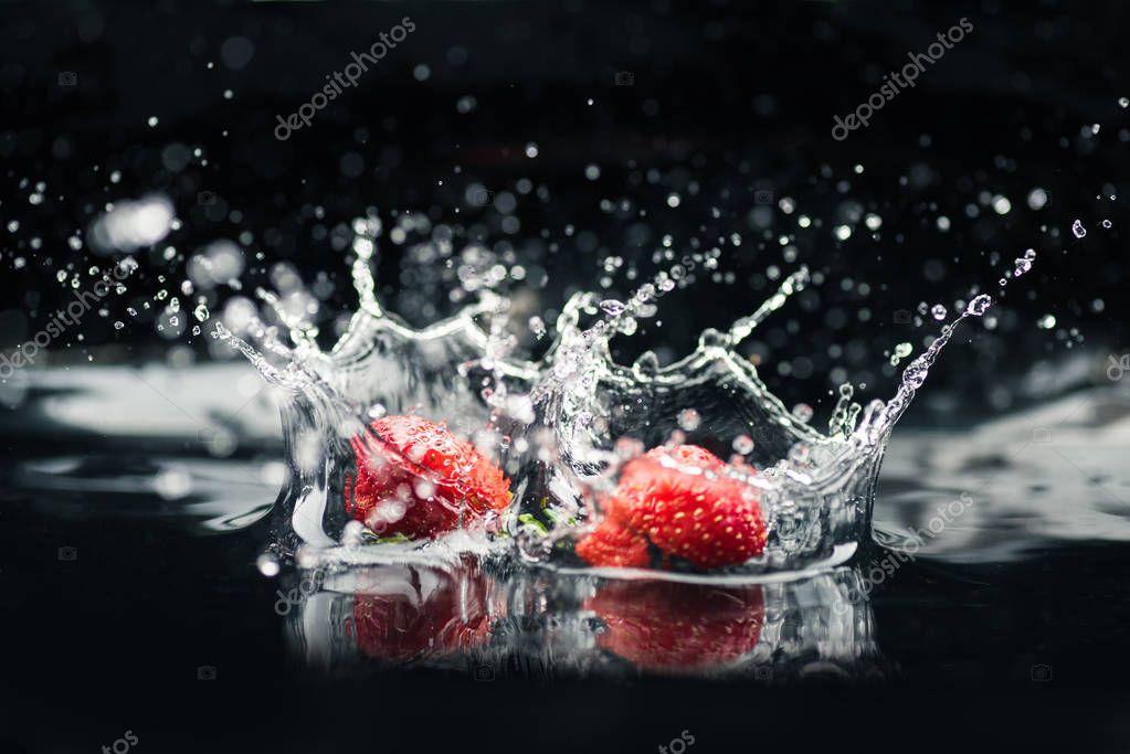 ripe strawberries falling in water