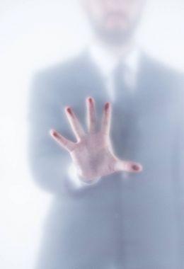 businessman gesturing behind glass