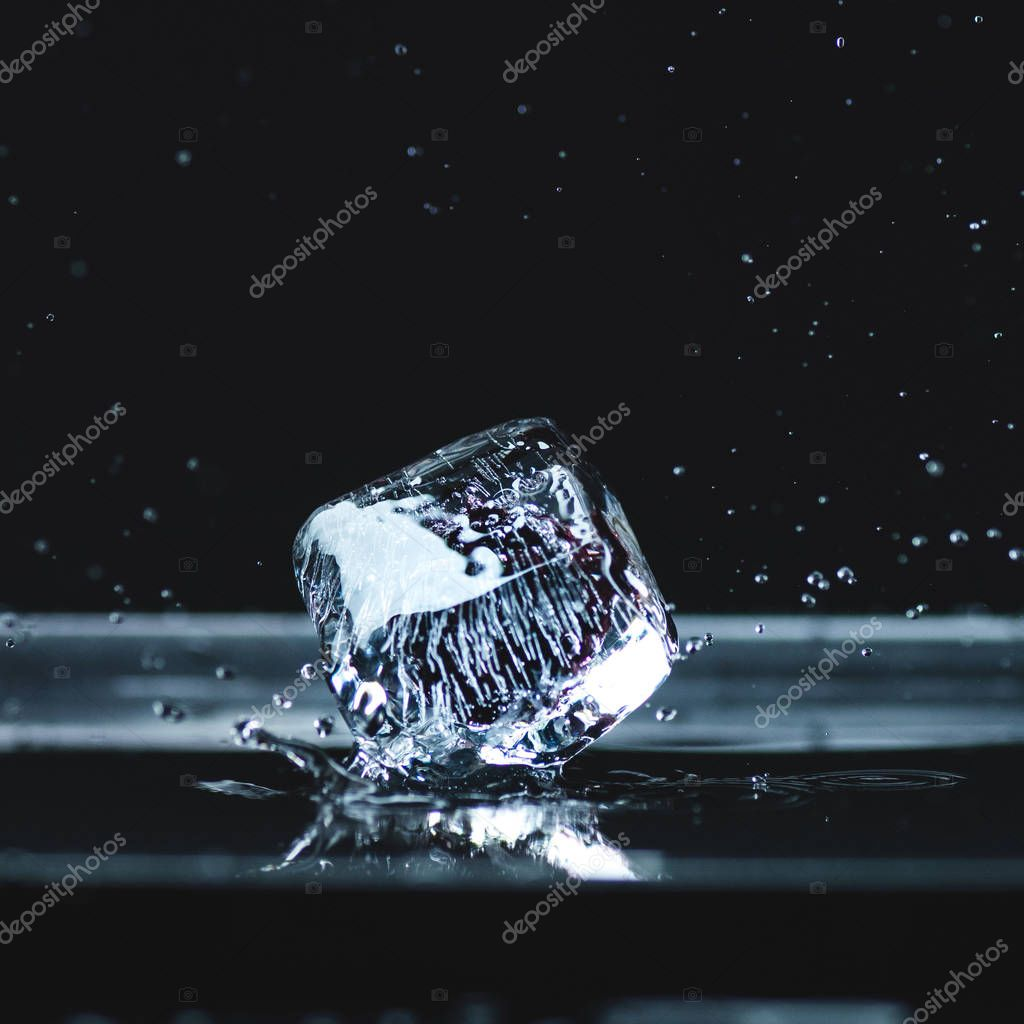 melting ice cube with water drops