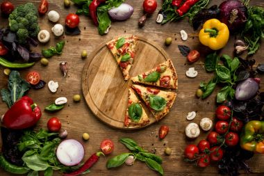 Flat lay with italian pizza slices on wooden board with various fresh vegetables and herbs on table stock vector