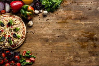 raw homemade pizza with ingredients