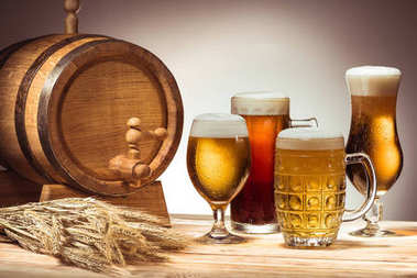 Barrel and different beer in glasses on wooden tabletop with wheat ears stock vector
