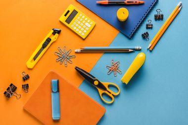 Composition of orange and blue school supplies with calculator stock vector