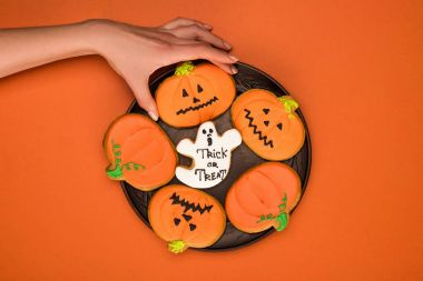 woman taking halloween cookie