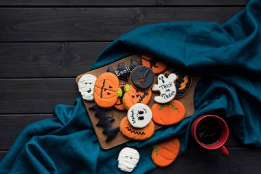 Composition of halloween cookies on wooden board and blue cloth with cup of coffee stock vector