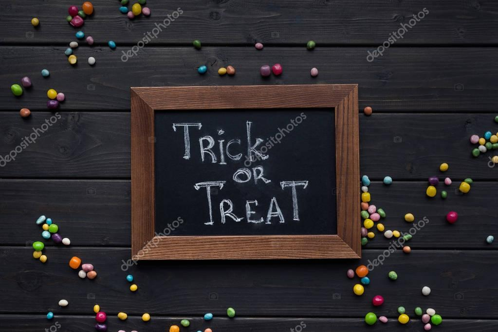 Top view of chalkboard with trick or treat inscription on table with colorful candies
