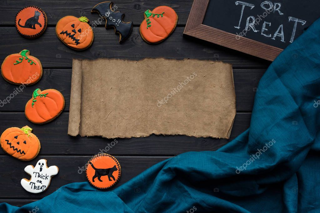 Top view of halloween composition with cookies and blank paper