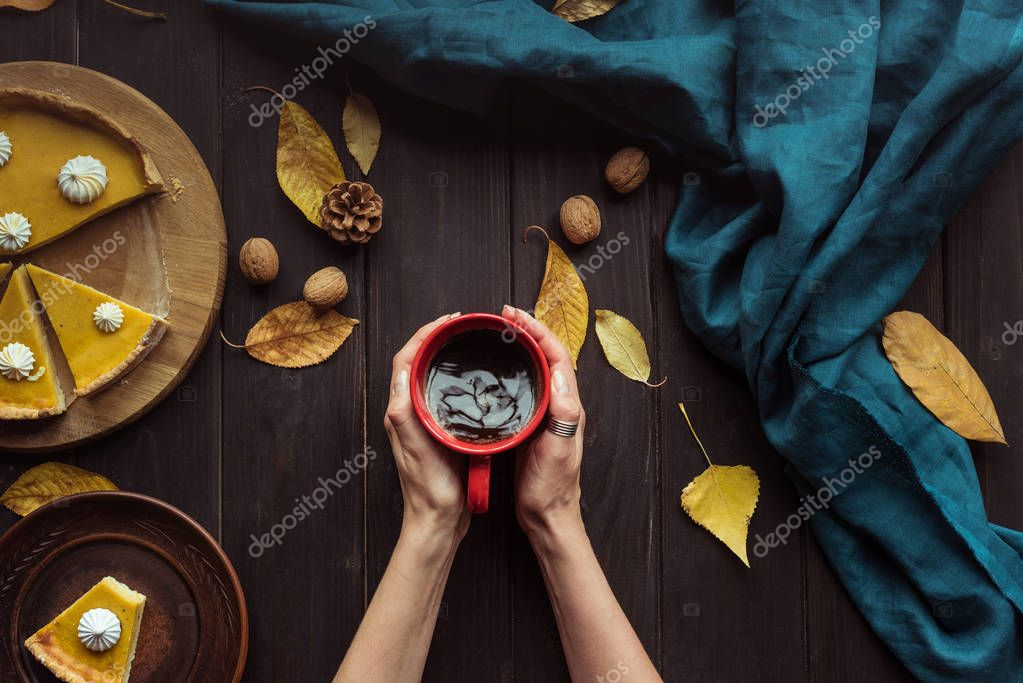 Top view shot of female hands holding a cup of coffee over a wooden table with pumpkin pie on it stock vector