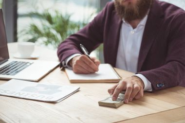 businessman writing and holding dollar