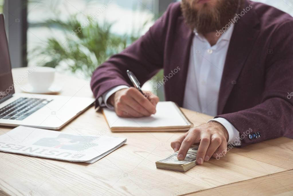 Cropped view of businessman writing and holding dollar banknotes, salary concept stock vector