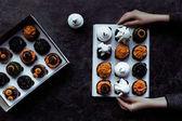 hands holding halloween cupcakes