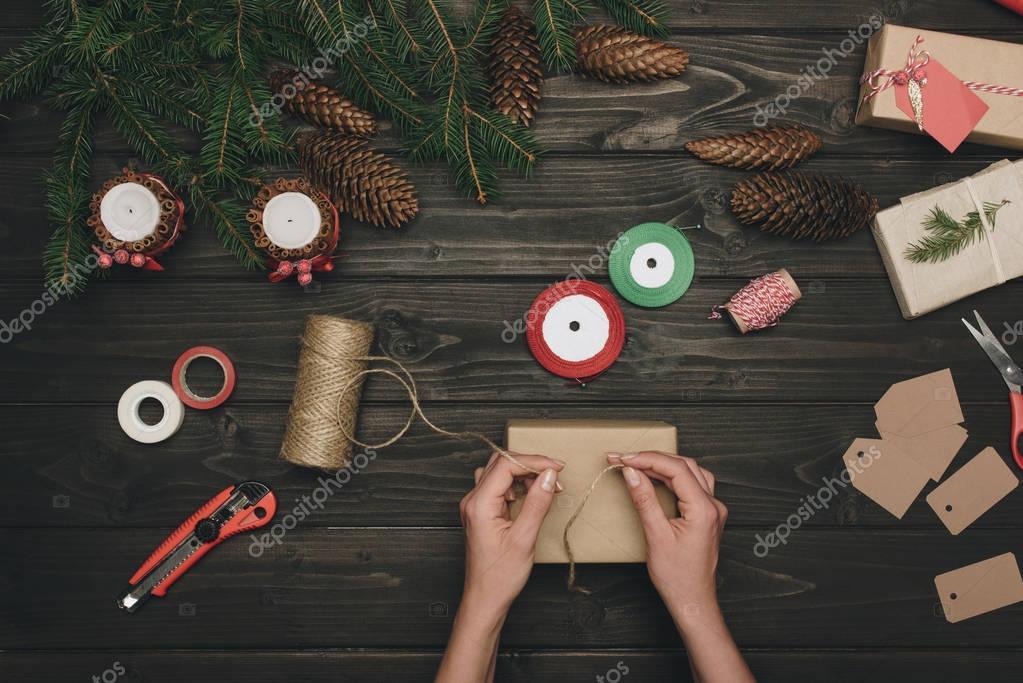 woman decorating christmas gift