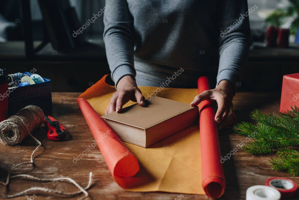 woman wrapping book as christmas gift