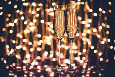 Selective focus of glasses of champagne against festive lights stock vector