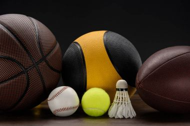 Closeup shot of various sports balls and shuttlecock on wooden surface stock vector