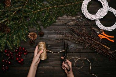 florist making Christmas wreaths