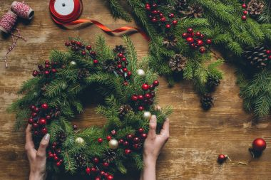 hands holding Christmas wreath