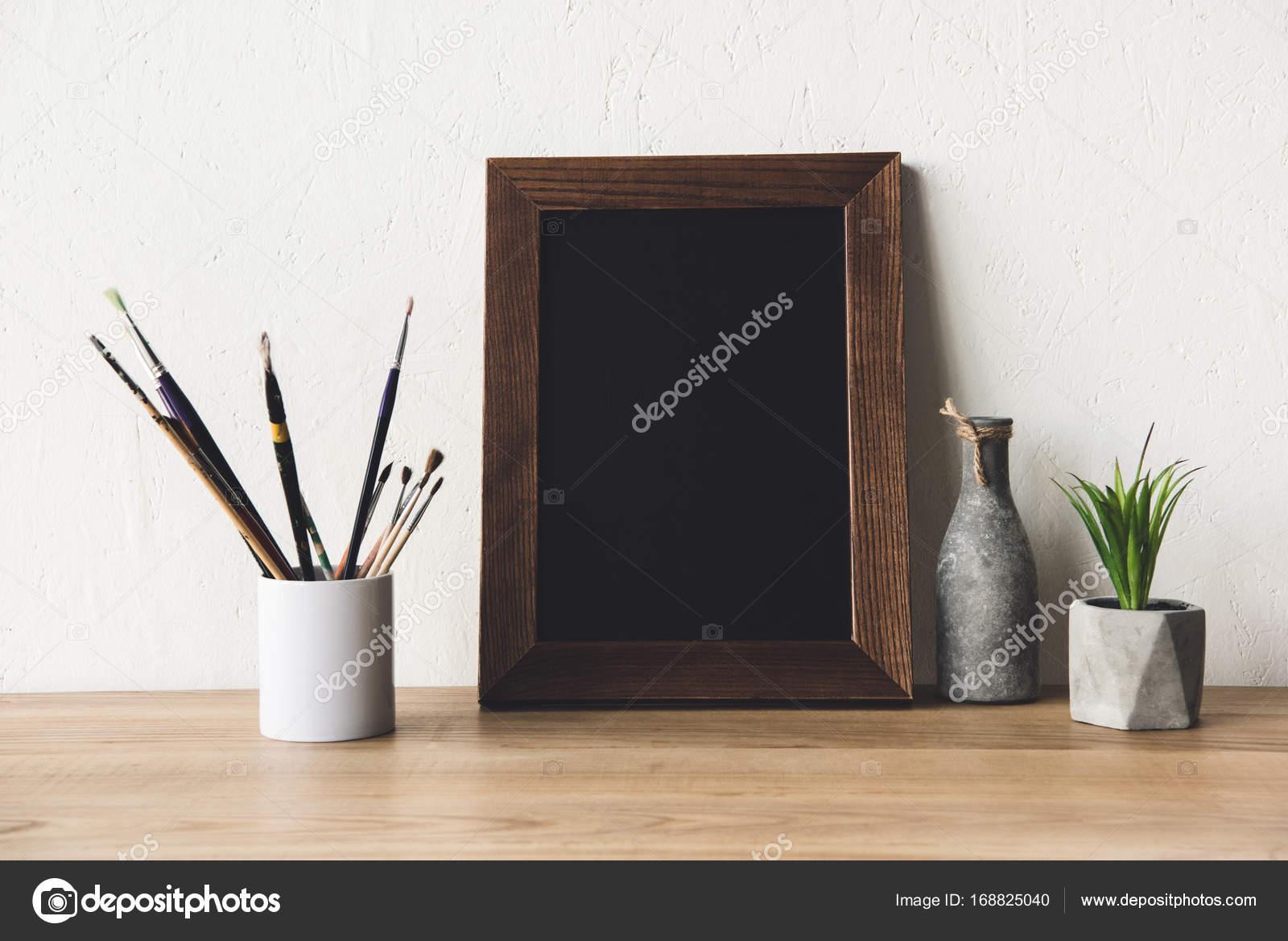 Photo frame and paintbrushes on tabletop stock photo close up view of empty photo frame vase and paintbrushes on wooden tabletop photo by vadimvasenin jeuxipadfo Choice Image