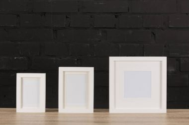 Close up view of empty photo frames on wooden tabletop stock vector
