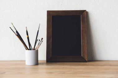 Photo frame and paintbrushes on tabletop