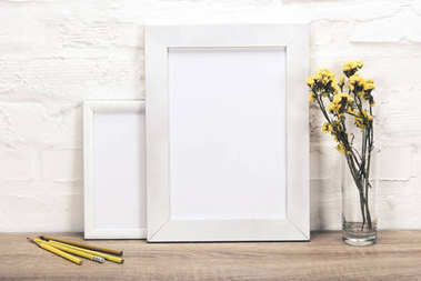 Empty photo frames and flowers in vase