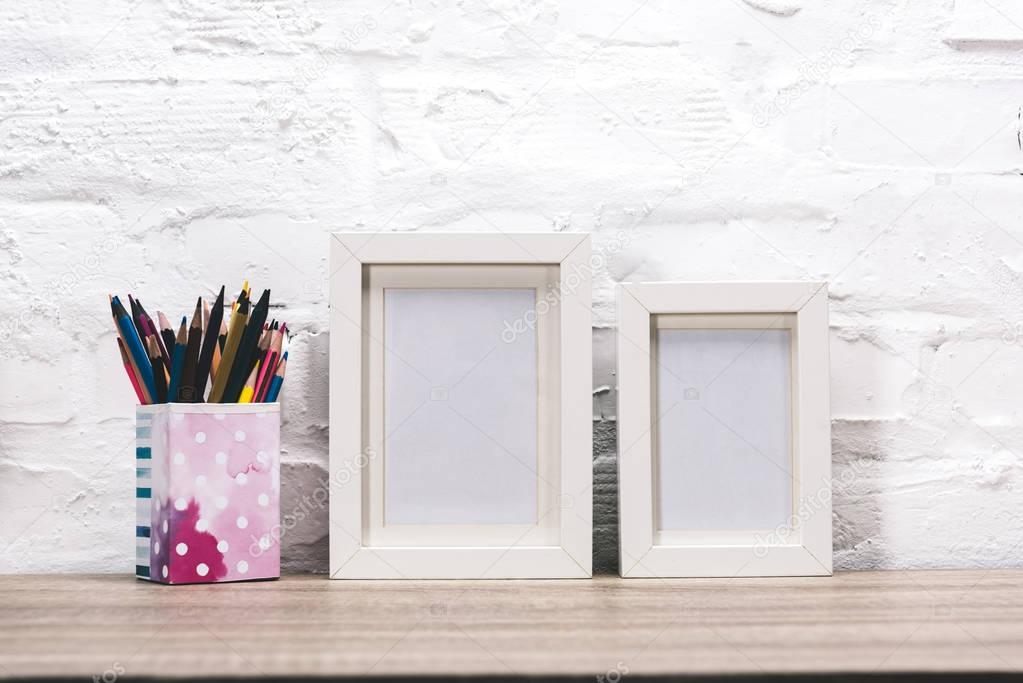 empty photo frames and pencils