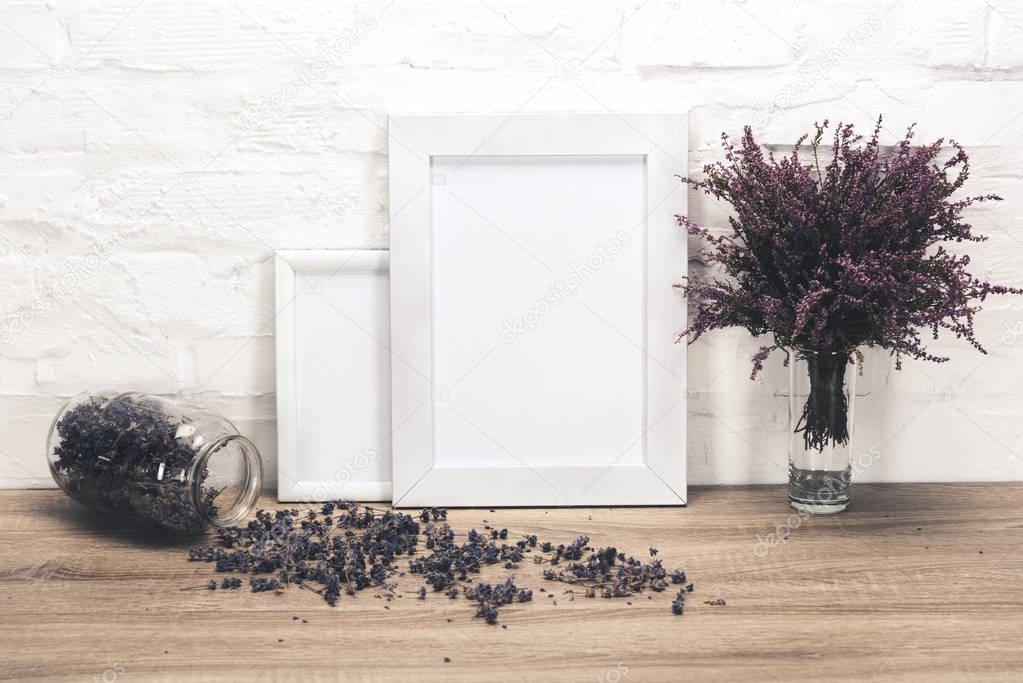 empty photo frames and flowers on table