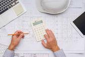 architekt pracoval s plány a kalkulačka