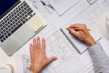 Cropped shot of architect writing in notebook while working on architectural project stock vector