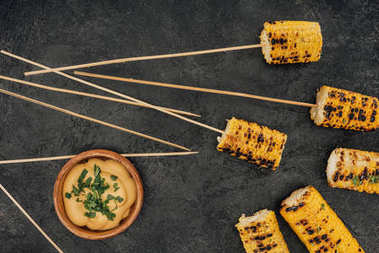 grilled corn pierced with sticks