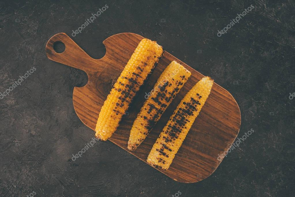 grilled corn on wooden cutting board