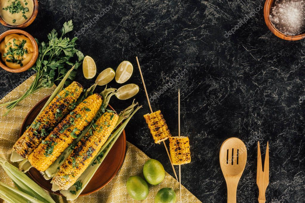 grilled corncobs with wooden spatulas