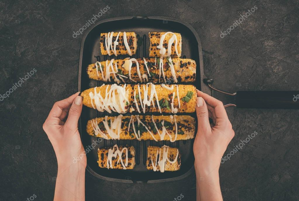 woman with baking tray of corn
