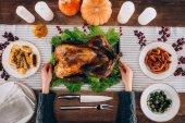 Photo Man serving baked turkey on table