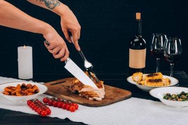 Man cutting baked turkey