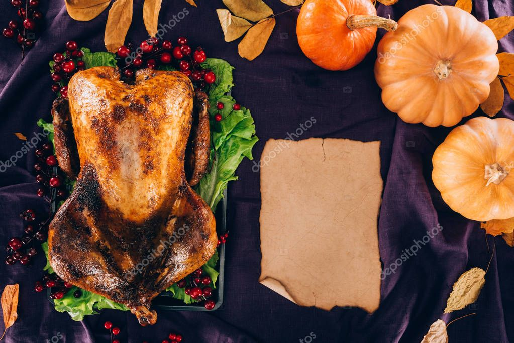 Baked turkey with pumpkins and sheet of paper