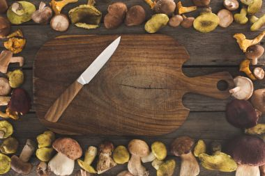 cutting board with knife and mushrooms around