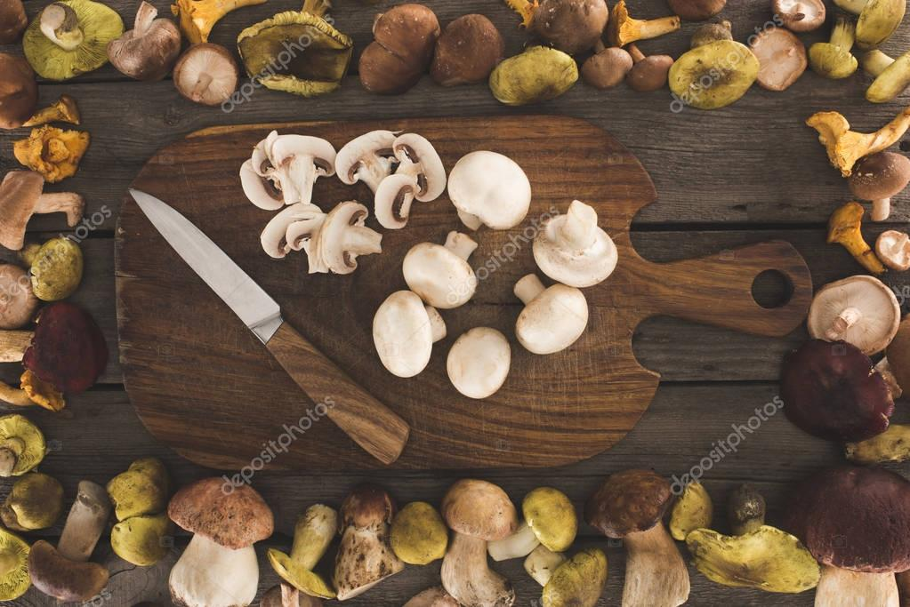 cutting board with knife and cut mushrooms