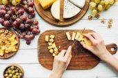 Fotografie žena řezání sýr