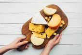 ruce a smíšený sýr na dřevěné desce