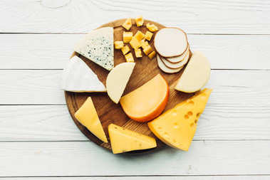 Top view of assorted various types of cheese on wooden cutting board stock vector