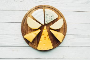 assorted types of cheese on cutting board