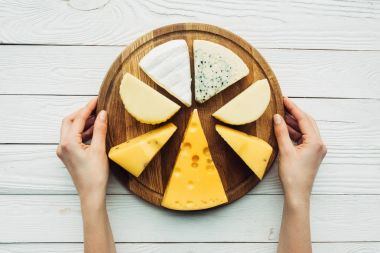 hands and wooden board with assorted cheese