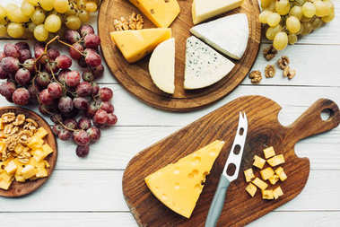 Flat lay with various types of cheese, grapes and knife on wooden surface stock vector