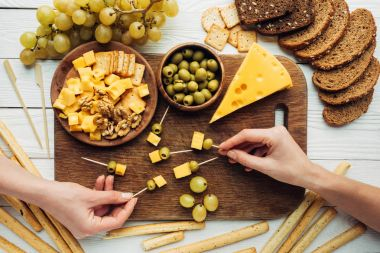 women making canapes with cheese