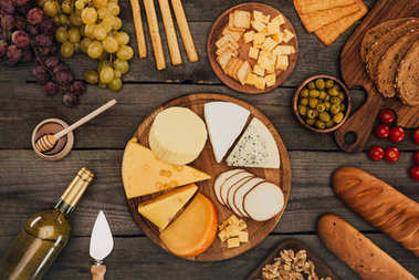 Flat lay of assortment of cheese types on cutting board, grapes, bottle of wine, honey and olives on wooden surface stock vector