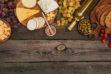 Flat lay with various types of cheese on cutting board, honey, bread, olives and bottle of wine on wooden tabletop stock vector