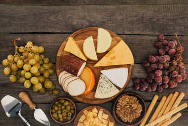 Top view of arranged various types of cheese on cutting board, olives, hazelnuts and grapes on wooden surface stock vector